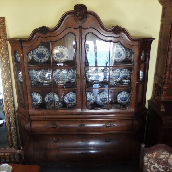 """ndauja, """"Chippendale"""" stiliaus XIXa. vid. Indauja sudaryta iš dviejų dalių: apatinė – 3 talpūs stalčiai, su reljefinėmis augalinėmis kompozicijomis, puoštais bronzos metalo spynelių apkalais bei rankenėlėmis. Viršutinis indaujos skyrius – vitrininio tipo spintelė, suskirstyta į lentynas viduje, su stiklo durelėmis."""