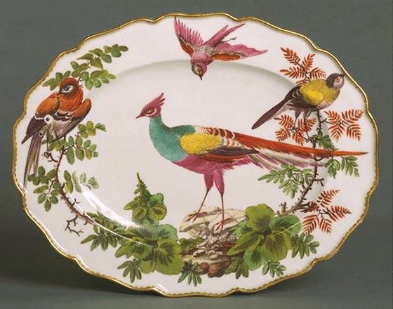 Chelsea manufaktūros porcelianinė lėkštė, Anglija, maždaug 1765 metai. Minkštasis porcelianas dekoruotas emalinėmis spalvomis ir auksuotais kraštais. (Victoria and Albert muziejus, Londonas)