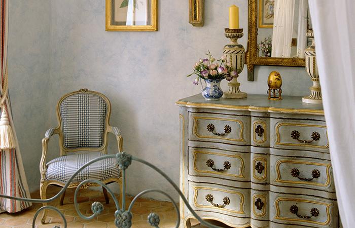 Kaldinta metalinė lova, nuostabi komoda ir krėslas prancūziškame miegamajame.